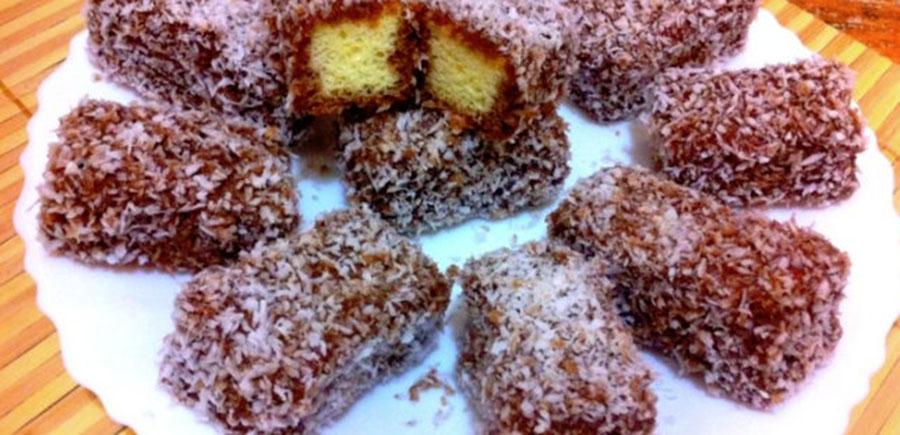 """Prăjitura """"Tăvălită"""" în nucă de cocos, o rețetă simplă cu blat pufos și sirop de ciocolată"""